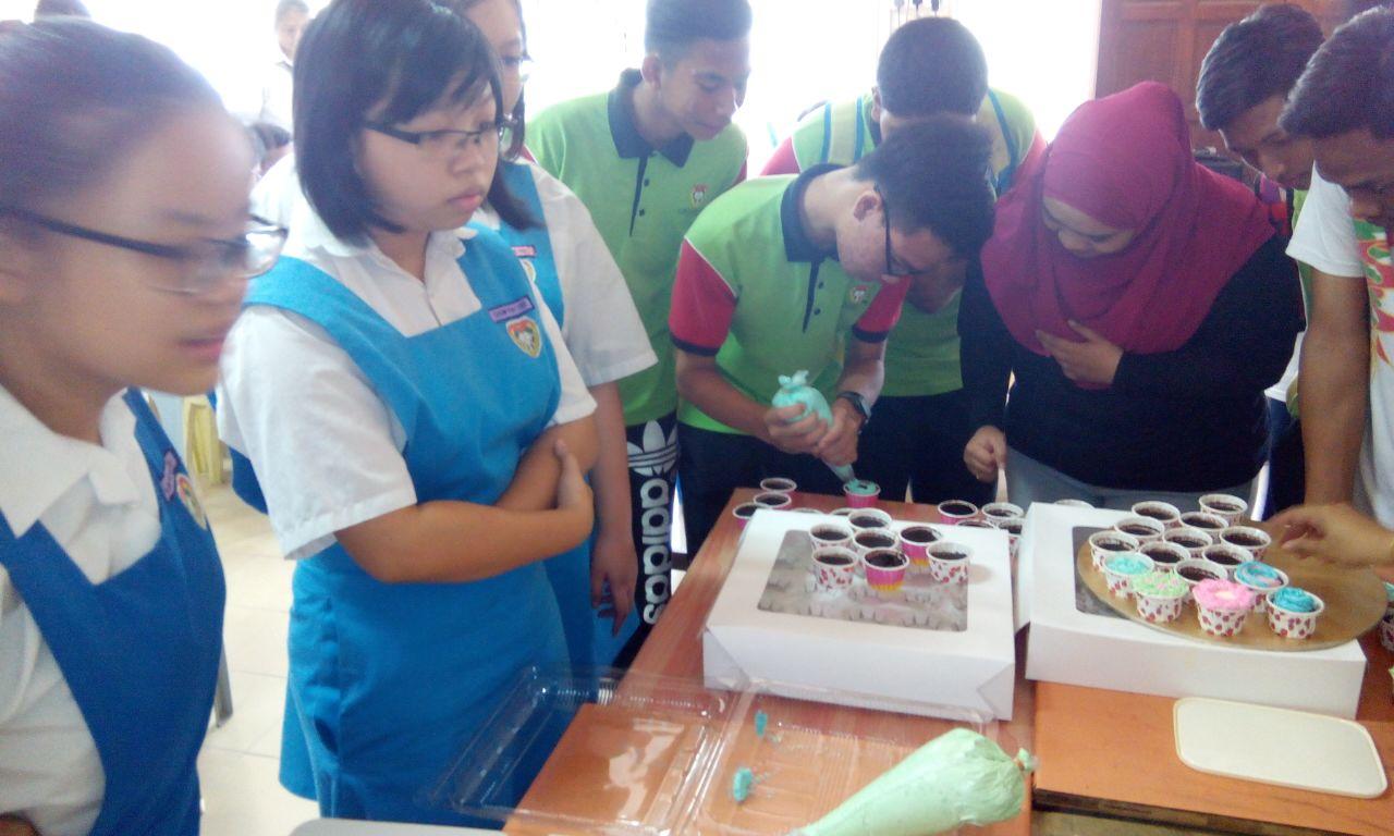Pelajar mengambil bahagian dalam mendekorasi kek